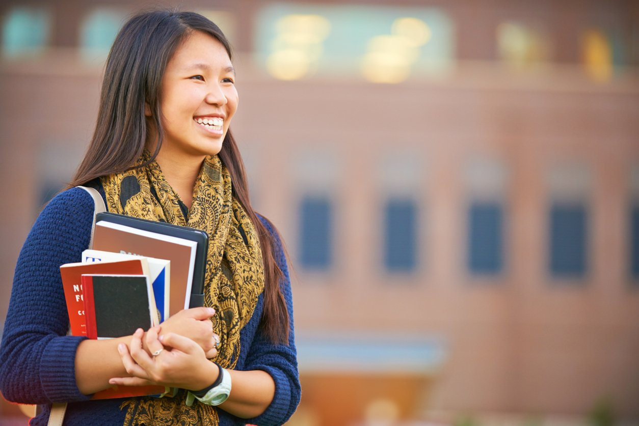 female-college-student-stands-smiling-while-holding-books-on-campus