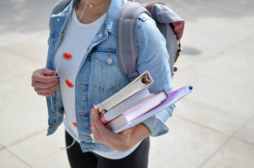 A woman wearing a denim jacket and a backpack holds a stack of books